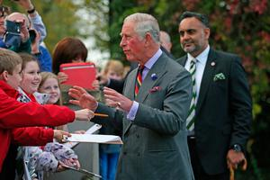The Prince of Wales meets well-wishers outside the Eglinton Community Centre in Londonderry during a visit to communities hit by the summer's flash floods. Laura Hutton/PA Wire