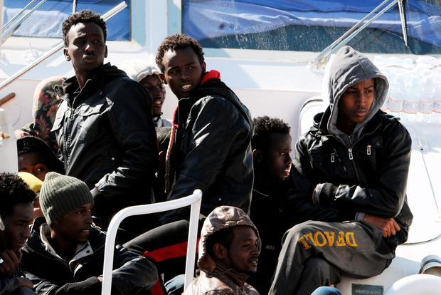 Migrants sit on the deck of an Italian Coastal Guard boat as they wait to disembark at Palermo's harbor, Italy, after being rescued at sea, Saturday, April 18, 2015.(AP Photo/Alessandro Fucarini)