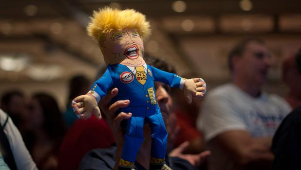 A supporter of Republican presidential candidate Donald Trump holds up a Trump doll during an election night party at a hotel in downtown Phoenix, Arizona on November 8, 2016.  Millions of Americans voted November 8th for their new leader in a historic election that will either elevate Democrat Hillary Clinton as their first woman president or hand power to maverick populist Donald Trump. / AFP PHOTO / Laura SegallLAURA SEGALL/AFP/Getty Images