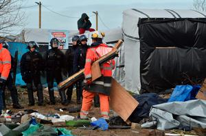 "A man sits on a shelter's roof in front of anti-riot policemen as agents dismantle shelters on February 29, 2016 in the ""jungle"" migrants and refugees camp in Calais, northern France.  A French court on February 25 gave the green light to plans to evacuate hundreds of migrants from the southern half of the sprawling camp in the port town, with many wanting to stay near the entrance to the Channel Tunnel, the gateway to their ultimate goal of Britain. AFP PHOTO / PHILIPPE HUGUENPHILIPPE HUGUEN/AFP/Getty Images"