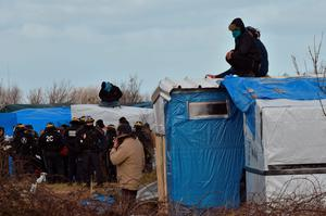 "People sit on a shelter's roof in front of anti-riot policemen as agents dismantle shelters on February 29, 2016 in the ""jungle"" migrants and refugees camp in Calais, northern France.  A French court on February 25 gave the green light to plans to evacuate hundreds of migrants from the southern half of the sprawling camp in the port town, with many wanting to stay near the entrance to the Channel Tunnel, the gateway to their ultimate goal of Britain. AFP PHOTO / PHILIPPE HUGUENPHILIPPE HUGUEN/AFP/Getty Images"