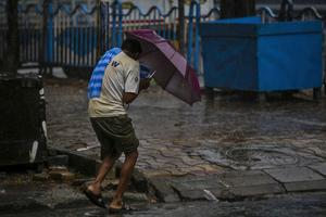 A man struggles to hold his umbrella amid the high winds in Kolkata (Bikas Das/AP)