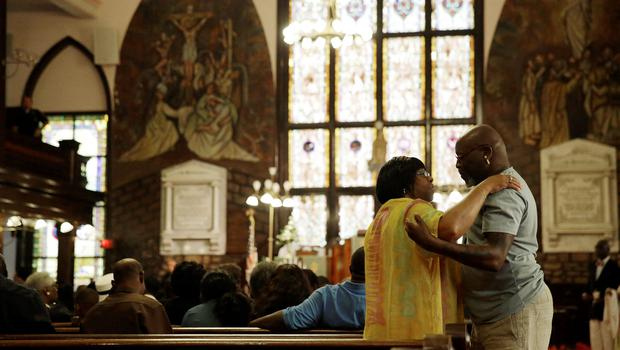 Church members embrace inside the church , Sunday, June 21, 2015, in Charleston, S.C., at the Emanuel A.M.E. Church four days after a mass shooting that claimed the lives of it's pastor and eight others. (AP Photo/David Goldman)
