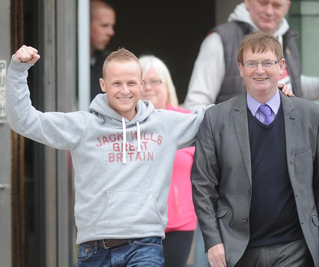 Loyalist Jamie Bryson punches the air as he leaves court after being given a six-month suspended sentence. Supporting him at court was victims' campaigner Willie Frazer. Photo by Alan Lewis.