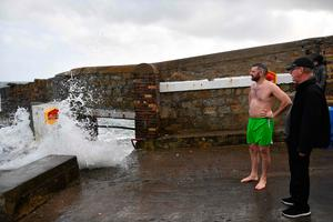 "A man takes a swim at the 40 Foot swimming area on the Irish Sea coast at Glenageary, County Dublin, on October 16, 2017 as Ireland braces for the passing of the storm Ophelia. Schools were closed on October 16 as Ireland braced for an ""unprecedented storm"", with authorities warning that violent winds, rain and storm surges could pose a risk to life.   / AFP PHOTO / Ben STANSALLBEN STANSALL/AFP/Getty Images"