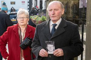 Patrick McElhone's sister Mary McCourt and brother Mickey with a photograph of his brother Patrick outside Omagh Court House on Thursday. Picture Martin McKeown. 21.01.21