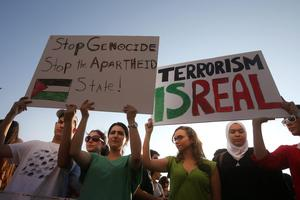 Lebanese and Palestinians hold up placards during a protest against the war in Gaza, in Beirut, Lebanon, Monday July 21, 2014. (AP Photo/Hussein Malla)