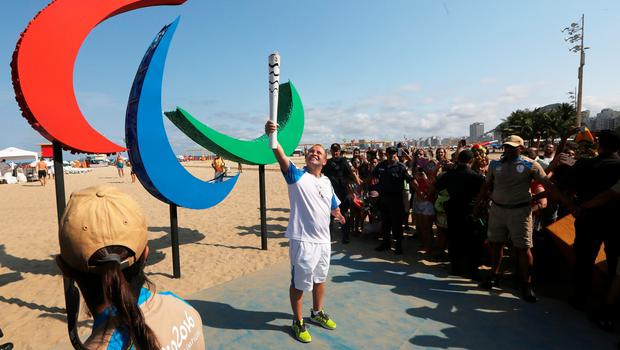 RIO DE JANEIRO, BRAZIL - SEPTEMBER 07:  A torch bearer poses in front of the Paralympic symbol, Agitos, during 2016 Paralympic Torch Relay along Copacabana beach before tonight's Opening Ceremonies on September 7, 2016 in Rio de Janeiro, Brazil. (Photo by Mario Tama/Getty Images)