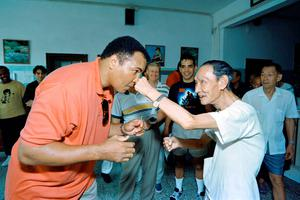 """This file photo taken on September 01, 1994 shows Boxing great Muhammad Ali receiving a punch from a 79 old """"sparring-partner"""" during a visit in a old people's home in Macau. Boxing legend Muhammad Ali, dies at 74. The former heavyweight world champion was hospitalized on Thursday at a Phoenix, Arizona, hospital with a respiratory issue, which US media reported was complicated by his Parkinson's disease.  / AFP PHOTO / Mike FialaMIKE FIALA/AFP/Getty Images"""