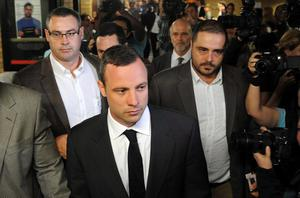 Oscar Pistorius, center front, arrives for his trial at the high court in Pretoria, South Africa, Monday, March 3, 2014. Pistorius is charged with murder with premeditation in the shooting death of girlfriend Reeva Steenkamp in the pre-dawn hours of Valentine's Day 2013. (AP Photo)