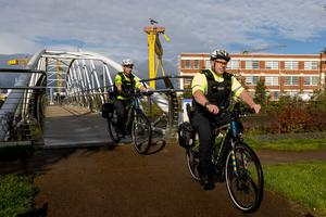 Neighbour Policing Team Officers riding the new electric bicycles across the Sam Thompson Bridge in Belfast. Liam McBurney/PA Wire