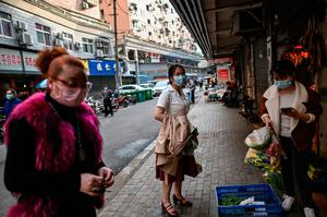 Women wearing face masks visit roadside food stalls in Wuhan in China's central Hubei province on April 8, 2020, as travel restrictions to halt the spread of the COVID-19 coronavirus were lifted in the city. Photo by Hector Retamal/AFP via Getty Images)