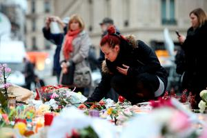 A woman joins crowds looking at floral tributes and candles left at Place de la Republique in Paris following the terrorist attacks on Friday evening. PRESS ASSOCIATION Photo. Picture date: Monday November 16, 2015. See PA story POLICE Paris. Photo credit should read: Steve Parsons/PA Wire