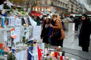 People look at floral tributes and candles left at Place de la Republique in Paris following the terrorist attacks on Friday evening. PRESS ASSOCIATION Photo. Picture date: Monday November 16, 2015. See PA story POLICE Paris. Photo credit should read: Steve Parsons/PA Wire