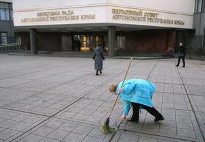 SIMFEROPOL, UKRAINE - MARCH 03:  A cleaning lady sweeps the courtyard of the Crimean Parliament building, which only days before had hostes barricades set up by pro-Russian militants, on March 3, 2014 in Simferopol, Ukraine. Police have removed roadblocks in the city center and access to the Crimean Parliament building is open again in signs that daily life is returning to a form of normalcy and that pro-Russian forces have cemented their control of the Crimean capital. Meanwhile world leaders have warned Russian President Vladimir Putin against further escalation that could spark war between Russia and Ukraine.  (Photo by Sean Gallup/Getty Images)