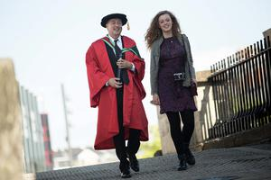 Cinematographer Seamus McGarvey received the honorary degree of Doctor of Fine Arts (DFA) for outstanding contributions to film making, contemporary art and cinematography. He is pictured here with daughter Stella. (Photo: Nigel McDowell/Ulster University)