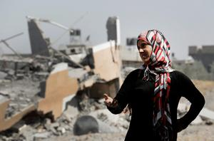 A Palestinian woman stands near the rubble of destroyed houses in the heavily bombed town of Beit Hanoun, Gaza Strip, close to the Israeli border, Friday, Aug. 1, 2014.  (AP Photo/Lefteris Pitarakis)
