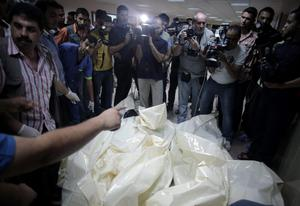 Photographers and cameramen photograph the bodies of six members of the Gharabli family who were killed in an Israeli strike, at the Shifa hospital in Gaza City, Monday, July 21, 2014.  (AP Photo/Khalil Hamra)