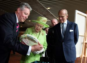 BELFAST, NORTHERN IRELAND - JUNE 27: Queen Elizabeth II and Prince Philip,Duke of Edinburgh admire a gift held by Northern Ireland First Minister Peter Robinson and watched by Deputy First Minister Martin McGuinness during a visit to the Lyric Theatre on June 27, 2012 in Belfast, Northern Ireland.  During the Queen's two day visit to Northern Ireland she held a hugely significant meeting with former IRA commander and deputy First Minister of Northern Ireland, Martin McGuinness at the Lyric Theatre today. The Queen will also visit the newly opened Titanic Museum and the town of Enniskillen. (Photo by Paul Faith - WPA Pool/Getty Images)
