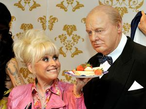 The TV star offers the wax figure of Sir Winston Churchill some lunch at Madame Tussauds in central London (John Stillwell/PA)