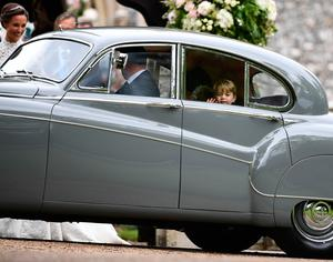 Britain's Prince George (R) waves as he leaves in a car after attending the wedding of his aunt, Pippa Middleton (L), to James Matthews at St Mark's Church in Englefield, west of London, on May 20, 2017. After turning heads at her sister Kate's wedding to Prince William, Pippa Middleton graduated from bridesmaid to bride on Saturday at a star-studded wedding in an English country church. The 33-year-old married financier James Matthews, 41, at a ceremony attended by the royal couple and tennis star Roger Federer, wearing a couture dress by British designer Giles Deacon.  / AFP PHOTO / POOL / Justin TALLISJUSTIN TALLIS/AFP/Getty Images