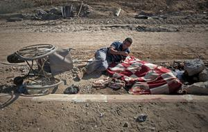 Palestinian Nidal Abu Rjeilah, 30, leans over the blanket-covered corpse of his disabled sister Ghadeer, 17, in the southern Gaza village of Khuzaa on Friday, Aug. 1, 2014. (AP Photo/Khalil Hamra)