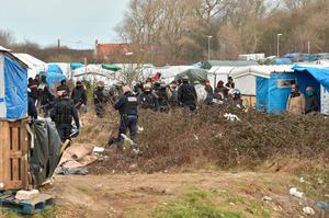 "Policemen look on as workers dismantle shelters in the ""jungle"" migrants and refugees camp in Calais, northern France. Pic: Getty Images"