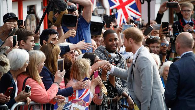Britain's Prince Harry greets well-wishers on the street outside Windsor Castle in Windsor on May 18, 2018, the eve of Prince Harry's royal wedding to US actress Meghan Markle.  Britain's Prince Harry and US actress Meghan Markle will marry on May 19 at St George's Chapel in Windsor Castle. / AFP PHOTO / Odd ANDERSENODD ANDERSEN/AFP/Getty Images