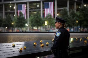 Port Authority Police Officer Donna Przybyszewski takes a moment to herself before family members are let in for the memorial observances held at the site of the World Trade Center in New York, Sept. 11, 2014. This year marks the 13th anniversary of the September 11th terrorist attacks that killed nearly 3,000 people at the World Trade Center, Pentagon and on Flight 93. (AP Photo/POOL, Andrew Burton)
