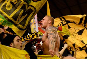 Borussia Dortmund fans cheer during the UEFA Europa league quarter-final second leg football match between Liverpool  and Borussia Dortmund at Anfield stadium in Liverpool on April 14, 2016. / AFP PHOTO / OLI SCARFFOLI SCARFF/AFP/Getty Images