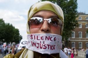 A female protester against military action in Gaza wears a 'Silence is injustice' sign as she marches through Westminster, central London. Picture date: Saturday July 26, 2014.