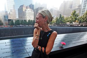 FILE - SEPTEMBER 10, 2014: This year marks the 13th anniversary of the September 11 terrorist attacks on the United States. Various events this week will honor those who lost their lives. NEW YORK, NY - SEPTEMBER 11:  Carrie Bergonia of Pennsylvania looks over the name of her fiance, firefighter Joseph Ogren at the 9/11 Memorial during ceremonies for the twelfth anniversary of the terrorist attacks on lower Manhattan at the World Trade Center site on September 11, 2013 in New York City. The nation is commemorating the anniversary of the 2001 attacks which resulted in the deaths of nearly 3,000 people after two hijacked planes crashed into the World Trade Center, one into the Pentagon in Arlington, Virginia and one crash landed in Shanksville, Pennsylvania. Following the attacks in New York, the former location of the Twin Towers has been turned into the National September 11 Memorial & Museum.  (Photo by Chris Pedota-Pool/Getty Images)