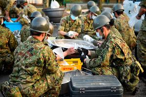 Members of the Japan Self-Defense Forces make rice balls at the soup-run operated at the evacuation center a day after the 2016 Kumamoto Earthquake at the Mashiki Town Hall on April 15, 2016 in Mashiki, Kumamoto, Japan. (Photo by Masterpress/Getty Images)