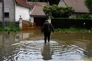 TOPSHOT - A resident walks accross a flooded street on June 1, 2016 in Nemours, southeast of Paris. Torrential downpours have lashed parts of northern Europe in recent days, leaving four dead in Germany, breaching the banks of the Seine in Paris and flooding rural roads and villages.  AFP PHOTO / DOMINIQUE FAGET / AFP PHOTO / DOMINIQUE FAGETDOMINIQUE FAGET/AFP/Getty Images