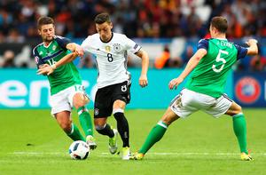 PARIS, FRANCE - JUNE 21:  Mesut Oezil (C) of Germany competes for the ball against Oliver Norwood (L) and Jonny Evans (R) of Northern Ireland  during the UEFA EURO 2016 Group C match between Northern Ireland and Germany at Parc des Princes on June 21, 2016 in Paris, France.  (Photo by Clive Mason/Getty Images)