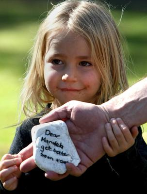 Avia Nossel with a stone bearing a get-well message, held by her father, outside the home of former president Nelson Mandela, in Johannesburg, on Saturday June 8, 2013. The stone was among others placed outside in flower beds from Mandela's previous hospital spells. (AP Photo)