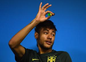 Figure it out: Neymar shows off a model of himself at yesterday's Brazil press conference