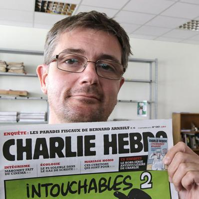 ADDS FULL NAME - FILE - In this Sept.19, 2012 file photo, Stephane Charbonnier also known as Charb , the publishing director of the satyric weekly Charlie Hebdo, displays the front page of the newspaper as he poses for photographers in Paris. Masked gunmen shouting Allahu akbar! stormed the Paris offices of a satirical newspaper Wednesday Jan.7, 2015, killing 12 people including Charb, before escaping. It was France's deadliest terror attack in at least two decades.  (AP Photo/Michel Euler, File)