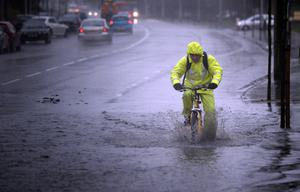 A hardy soul ames his wy home through the rain and puddles in Belfast this afternoon as the wet weather continued. Picture Charles McQuillan/Pacemaker.