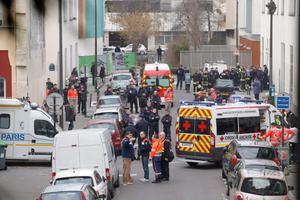 Ambulances gather in the street outside the French satirical newspaper Charlie Hebdo's office, in Paris, Wednesday, Jan. 7, 2015. Masked gunmen stormed the offices of a French satirical newspaper Wednesday, killing at least 11 people before escaping, police and a witness said. The weekly has previously drawn condemnation from Muslims. (AP Photo/Francois Mori)