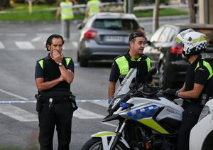 A police officer touches his face in Las Ramblas, in Barcelona, Spain, Friday, Aug. 18, 2017. A white van jumped up onto a sidewalk and sped down a pedestrian zone Thursday in Barcelona's historic Las Ramblas district, swerving from side to side as it plowed into tourists and residents. Police said 13 people were killed and more than 50 wounded in what they called a terror attack.(AP Photo/Manu Fernandez)