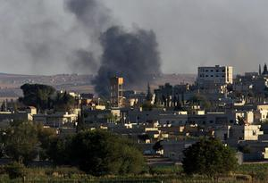 Smokes rise after a mortar shell landed in the south of the city center of Syrian Kurdish town of Kobani, seen from the Turkish side of border as thousands of new Syrian refugees from Kobani arrive in Suruc, Turkey, Wednesday, Oct. 1, 2014. U.S.-led coalition airstrikes targeted Islamic State fighters pressing their offensive against a Kurdish town near the Syrian-Turkish border on Tuesday in an attempt to halt the militants' advance, activists said.(AP Photo/Burhan Ozbilici)