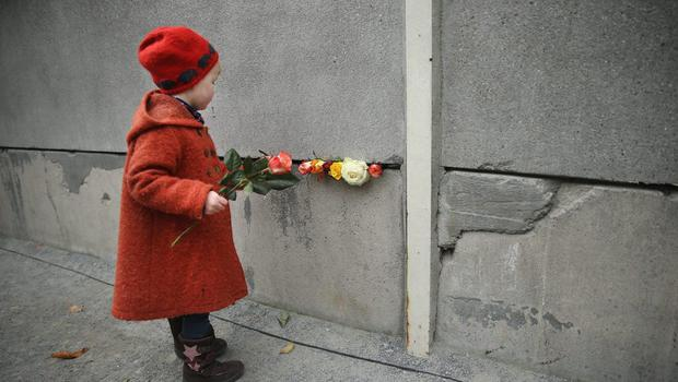 Hulda, 3, places flowers in between slats of the former Berlin Wall at the Berlin Wall Memorial at Bernauer Strasse on the 25th anniversary of the fall of the Wall on November 9, 2014 in Berlin, Germany.  (Photo by Sean Gallup/Getty Images)