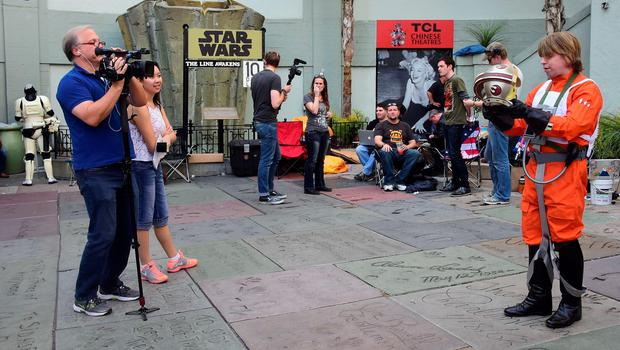 """Gerrard Christian Zacher, dressed in a Luke Skywalker X-Wing Pilot outfit, displays the helmet for a camera crew on hand to interview fans, among a group of over 100 people, who are free to come and go with their names on a list and tickets in their possession, for the December 17 opening of the new Star wars film """"The Force Awakens"""" on December 8, 2015. Some have been camped out for three nights in front of the TCL Theater along Hollywood Boulevard in Hollywood, California. AFP PHOTO / FREDERIC J. BROWNFREDERIC J. BROWN/AFP/Getty Images"""