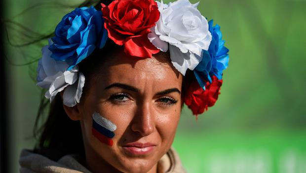 A woman with a Russian national flag painted on her cheek looks on before the Russia 2018 World Cup Group A football match between Russia and Egypt, at the Fan Zone in Kaliningrad on June 19, 2018. / AFP PHOTO / Ozan KOSEOZAN KOSE/AFP/Getty Images