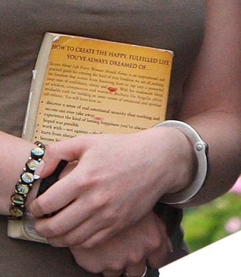 Michaella McCollum Connolly, handcuffed, arrives for a court hearing in Lima, Peru, clutching the book 'Secrets About Life Every Woman Should Know: Ten principles for spiritual and emotional fulfillment' (AP Photo/Karel Navarro)
