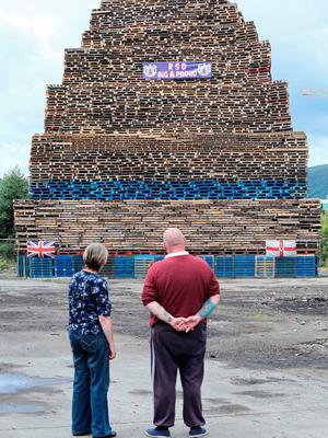 Former Bonfire builder Colin Tweedie (R), inspects a bonfire in the village area of Belfast on July 10, 2017, ahead of the traditional 11th night bonfires. [Photo: Paul Faith/AFP/Getty Images]
