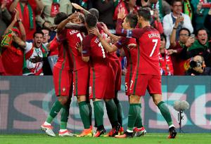 Portugal players celebrate after Nani, 2nd left, scored the opening goal during the Euro 2016 Group F soccer match between Portugal and Iceland at the Geoffroy Guichard stadium in Saint-Etienne, France, Tuesday, June 14, 2016. (AP Photo/Pavel Golovkin)