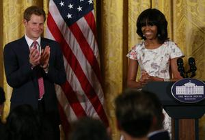 WASHINGTON, DC - MAY 09:  HRH Prince Harry (L), stands with first lady Michelle Obama during an event to honor military families at the White House on May 9, 2013 in Washington, DC. Prince Harry will be undertaking engagements on behalf of charities with which the Prince is closely associated on behalf also of HM Government, with a central theme of supporting injured service personnel from the UK and US forces.  (Photo by Mark Wilson/Getty Images)