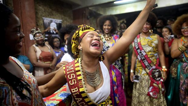 Maria Prisele (C) celebrates after winning the Miss Black Power competition on November 8, 2014 in Rio de Janeiro, Brazil. The non-traditional beauty competition featured black women solely with natural hair as a statement against traditional European standards of beauty and an affirmation of black identity.  (Photo by Mario Tama/Getty Images)